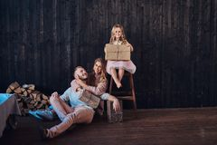 Family concept. Mom, dad and daughter together with gifts in empty room against the wooden wall. Family concept. Happy Mom, dad and daughter together with gifts royalty free stock photos