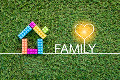 Family concept with house toy on green grass. Texture background royalty free stock photo
