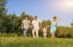 Family Concept and Ideas. Happy Family of Four Running Together Stock Photo