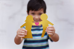 Family concept with little boy holding up paper chain shaped like a traditional couple with heart stock photography