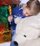 Family concept. Little boy hugging a teddy bear. In his hand the child is holding a large lollipop. Child in blue sweater Stock Photos