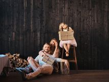 Family concept. Mom, dad and daughter together with gifts in empty room against the wooden wall. Family concept. Happy Mom, dad and daughter together with gifts stock image