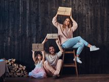 Family concept. Mom, dad and daughter together with gifts in empty room against the wooden wall. Family concept. Happy Mom, dad and daughter together with gifts royalty free stock photo