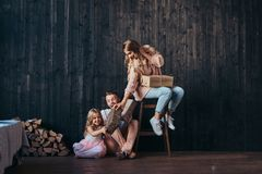 Family concept. Mom, dad and daughter together with gifts in empty room against the wooden wall. Family concept. Happy Mom, dad and daughter together with gifts stock photos