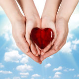 Family concept - mother's hands holding child hands with heart. Family concept - mother's hands holding child hands with glass heart at blue sky background royalty free stock photo