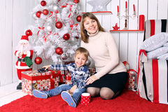 Family concept. Mother and son sitting under the Christmas tree Stock Images