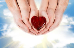Family concept - parents' hands holding child hands with heart Stock Image
