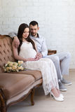 Family concept - portrait of young beautiful pregnant couple sit Stock Photos