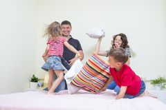 Young Caucasian Family of Four Having a Playful Funny Pillow Fight on Bed Indoors. Stock Images