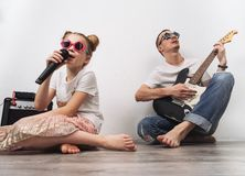 Family concert: a young girl sings with a microphone. Father plays the guitar. Portrait stock images