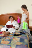 The family conflict. The young wife cleaning a room quarrels with the husband lying on a bed. The family conflict Royalty Free Stock Images