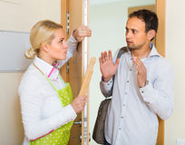 Family conflict at the door. Serious conflict between wife and husband at the door Royalty Free Stock Photo