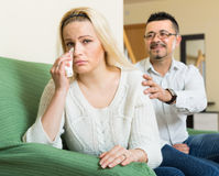 Family conflict at home. Man consoling depressed crying young women on sofa at home Stock Photo