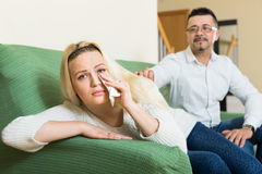 Family conflict at home. Man consoling young depressed crying women at home Stock Photo