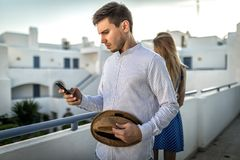 Family couple conflict between husband and wife. Guy man looks smartphone or dials. Family couple conflict between husband and wife. Guy men looks at smartphone stock photo
