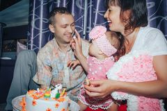 Family consisting father, mother and daughter celebrate birthday of one-year-old girl royalty free stock photos
