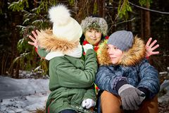 Family consisting mom, boy and girl in snow forest in a winter day. Teenagers and mother having picnic outdoor royalty free stock photos