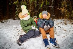 Family consisting mom, boy and girl in snow forest in a winter day. Teenagers and mother having picnic outdoor stock image