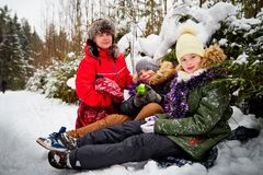 Family consisting mom, boy and girl in snow forest in a winter day. Teenagers and mother having picnic outdoor royalty free stock images