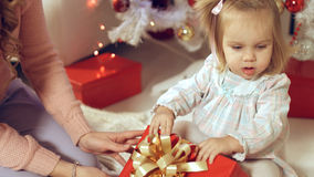 Family consists of the females sitting around the Christmas tree with gifts. Family consists of females sitting around the Christmas tree with gifts Royalty Free Stock Photos