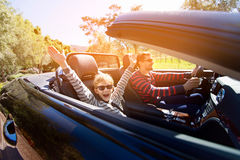 Family in convertible car. Excited family of two, young father and his smiling son with hands high up in the air, enjoying road trip in convertible car, journey Royalty Free Stock Image