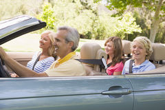 Family in convertible car smiling