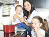 A family cook pasta inside the kitchen Stock Photos