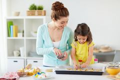 Happy mother and daughter making cookies at home. Family, cooking and baking concept - happy mother and little daughter with chocolate sprinkles decorating stock images