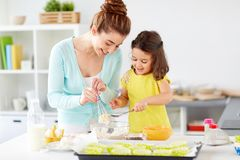 Happy mother and daughter baking muffins at home Royalty Free Stock Photo