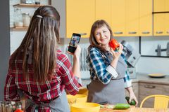 Family cooking blog women healthy lifestyle diet. Family cooking blog. Women mother daughter taking photos with smartphone promoting healthy lifestyle diet stock images