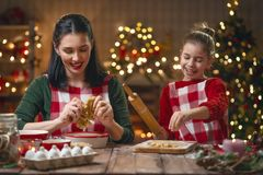 Family cooking Christmas cookies. Merry Christmas and Happy Holidays. Family preparation holiday food. Mother and daughter cooking cookies royalty free stock images