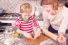 Family cooking at christmas time. Cheerful kid cutting dough for gingerbread cookies, family of mother and son enjoying christmas time at home Stock Photography