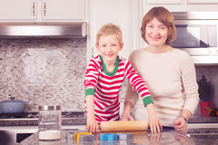 Family cooking at christmas time. Cheerful kid rolling dough for gingerbread cookies, family of mother and son enjoying christmas time at home Stock Image