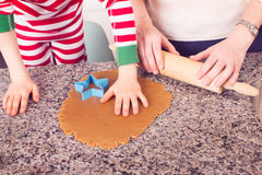 Family cooking at christmas time. Family enjoying making gingerbread cookies at home at cozy christmas time Royalty Free Stock Photos