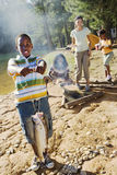 Family cooking food on camping trip beside lake, boy (8-10) holding aloft fish in foreground, smiling, portrait.  Royalty Free Stock Photography