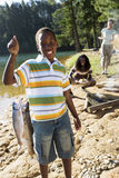 Family cooking food on camping trip beside lake, boy (8-10) holding aloft fish in foreground, smiling, portrait stock photography