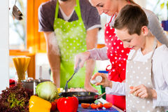 Family cooking healthy food in domestic kitchen. Family with Parents and children preparing healthy meal in domestic kitchen, having fun stock photography