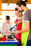 Family cooking healthy food in domestic kitchen Royalty Free Stock Images