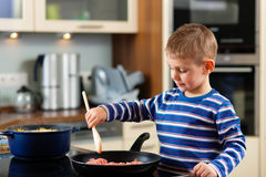 Family cooking in kitchen. Family cooking in their kitchen – the son is taking care fort he shopped meet royalty free stock photo