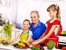 Family cooking at kitchen. Big family cooking at kitchen. Grandfather and children royalty free stock photos