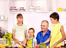 Family cooking at kitchen. Big family cooking at kitchen. Grandfather and children stock images