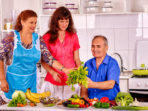 Family cooking at kitchen. Big family cooking at kitchen. Grandfather and grandmother with adult daughter stock images