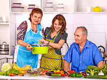 Family cooking at kitchen. Big family cooking at kitchen. Grandfather and grandmother with his adult daughte royalty free stock photo