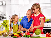 Family cooking at kitchen. Big family cooking at kitchen. Grandfather preparing food with his children royalty free stock photography