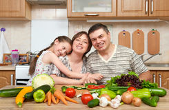 Family cooking in kitchen interior at home, fresh fruits and vegetables, healthy food concept, woman, man and children. Family cooking in kitchen interior at stock image