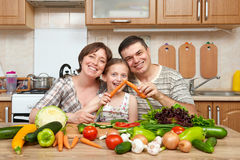 Family cooking in kitchen interior at home, fresh fruits and vegetables, healthy food concept, woman, man and children Stock Photos
