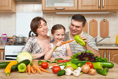 Family cooking in kitchen interior at home, fresh fruits and vegetables, healthy food concept, woman, man and children Stock Photo