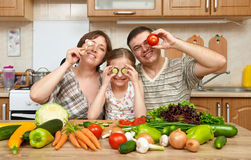 Family cooking in kitchen interior at home, fresh fruits and vegetables, healthy food concept, woman, man and children. Family cooking in kitchen interior at royalty free stock image