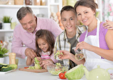 Family cooking at kitchen. Portrait of a happy family cooking together at kitchen royalty free stock images