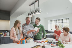 Happy Father`s Day, Dad!. Family are cooking a meal together in the kitchen. The two children are surprising their father with Father`s Day cards and presents royalty free stock images